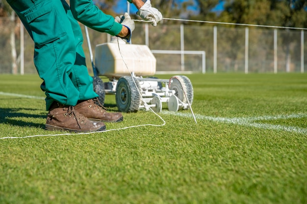 Растяжка веревки для облицовки футбольного поля белой краской на траве