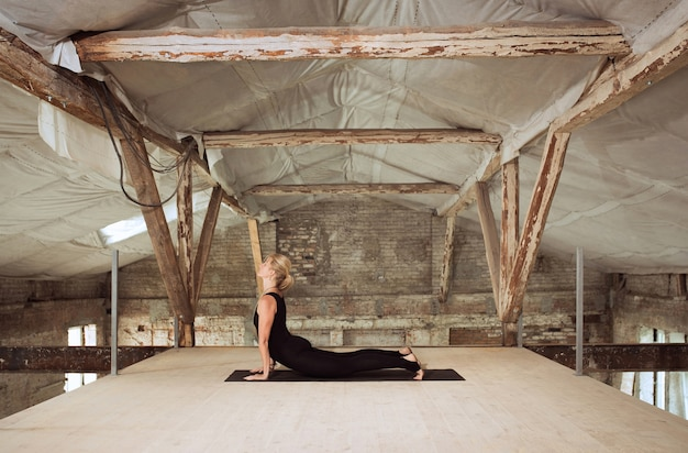 스트레칭. 젊은 체육 여자 버려진 된 건설 건물에 요가 연습. 정신적 및 신체적 건강 균형. 건강한 라이프 스타일, 스포츠, 활동, 체중 감소, 집중력의 개념.