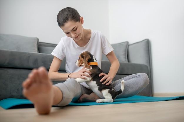 Растяжка. молодая женщина тренируется, пока ее щенок сидит рядом с ней