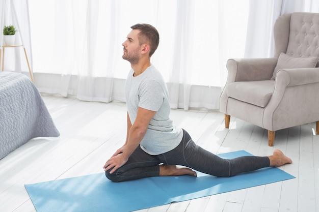 ストレッチ活動。運動をしながらヨガマットに座っている真面目なナイスマン