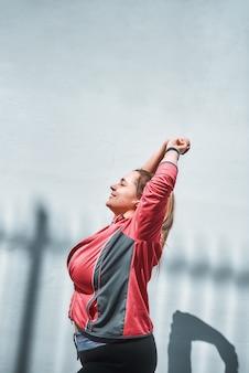 スポーツウェアのウォーミングアップで若いプラスサイズの女性のトレーニング後の側面図を伸ばす