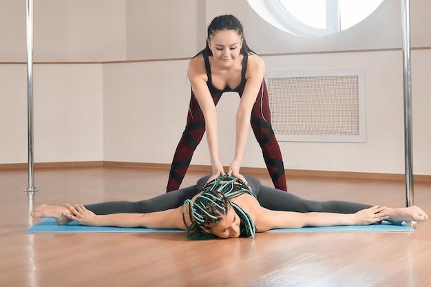Упражнения на растяжку и гибкость на занятиях в студии фитнеса на пилоне, тренер помогает студенту во время тренировки.