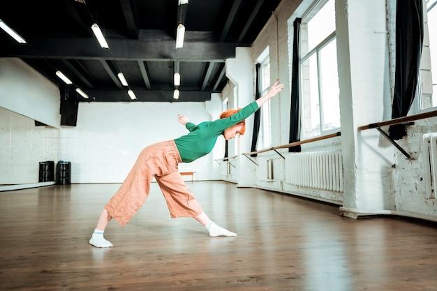 アサナを伸ばす。緑のタートルネックを身に着けてストレッチのためのアーサナをしている心地よい見た目のフィットヨガインストラクター