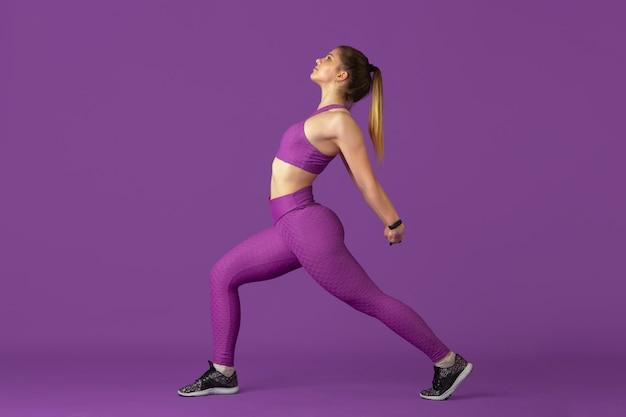 ストレッチ。紫のモノクロのポートレートで練習する美しい若い女性アスリート。陽気な白人フィット モデル トレーニング。ボディビルディング、健康的なライフスタイル、美しさ、アクションのコンセプト。