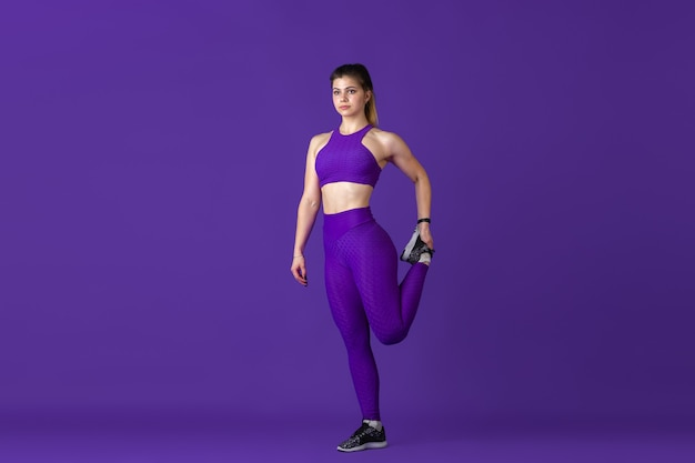 스트레칭. 스튜디오에서 연습하는 아름다운 젊은 여성 운동선수, 단색 보라색 초상화.