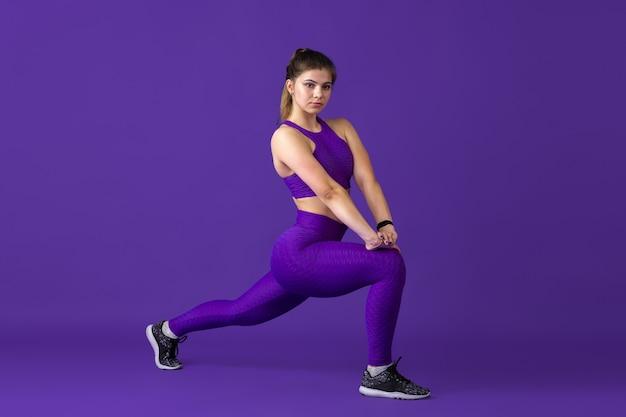Растяжка. красивая молодая спортсменка практикует, монохромный фиолетовый портрет. тренировка спортивной модели кавказской формы. бодибилдинг, здоровый образ жизни, красота и концепция действий.