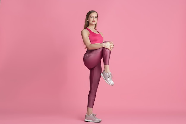 Stretching. beautiful young female athlete practicing in studio, monochrome pink portrait.