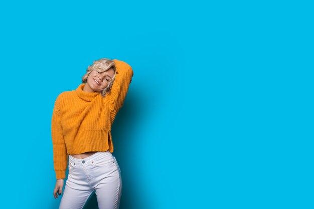 Растяжка блондинка позирует в желтом свитере на синей стене с свободным пространством