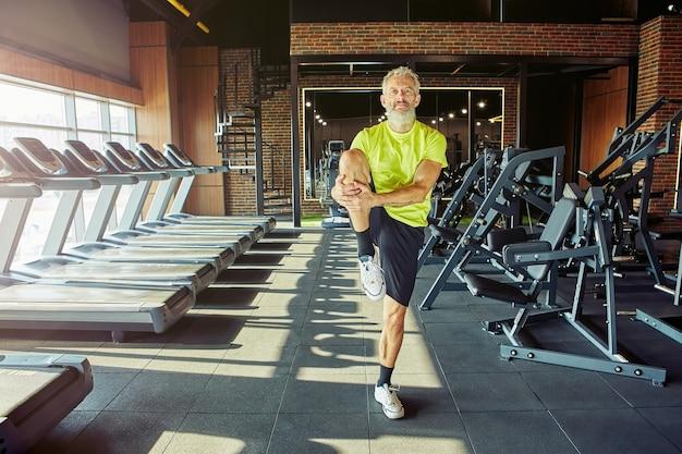 トレーニング前にウォーミングアップするスポーツウェアの中年男性のストレッチ体の肖像画