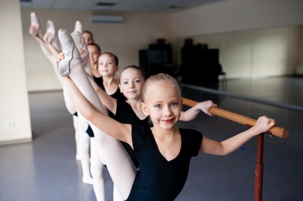 Растяжка, дети в классе балетных танцев.