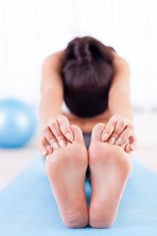 Упражнение на растяжку. вид спереди молодой женщины, растягивающейся на коврике для йоги