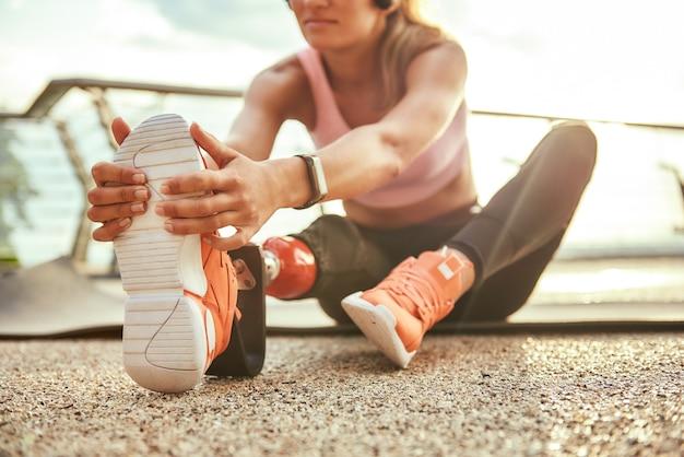 Обрезанное фото молодой красивой женщины в наушниках с протезом ноги, упражнения на растяжку