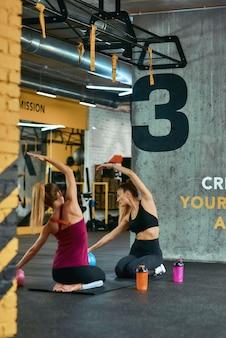 스트레칭 운동. 운동복을 입은 두 젊은 운동 여성의 세로 샷은 체육관 바닥에 앉아 운동하기 전에 워밍업을 하고 있습니다. 스포츠, 훈련, 웰빙 및 건강한 라이프 스타일