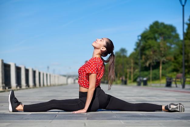 Stretching gymnast woman doing split, twine in city