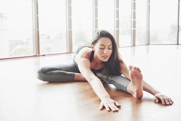Stretching a gymnast woman makes a split, a twine in a gym.
