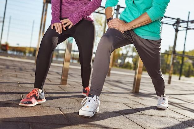 Обрезанное фото пары в спортивной одежде, разминки на стадионе, мужчина и женщина