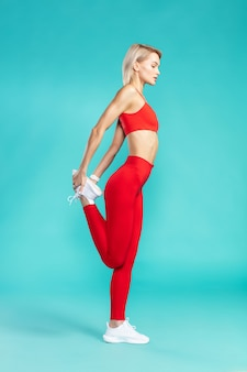 前にウォーミングアップする赤いスポーツウェアの若い魅力的なブロンドの女性のストレッチ脚の側面図