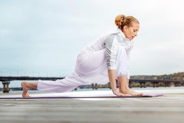 筋肉を伸ばす。彼女の筋肉に役立つストレッチ運動を行う若い女性