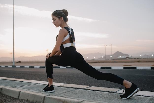 Растяжка на дороге в тропической стране радостной красивой женщины в солнечное утро. тренировка сильной спортсменки, энергии, мотивации, здорового образа жизни, тренировки на солнышке