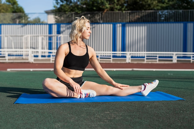 Stretching pose on mat at stadium