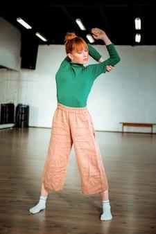 ストレッチ。ストレッチのためにアーサナをしている緑のタートルネックを身に着けているかなり赤い髪の少女