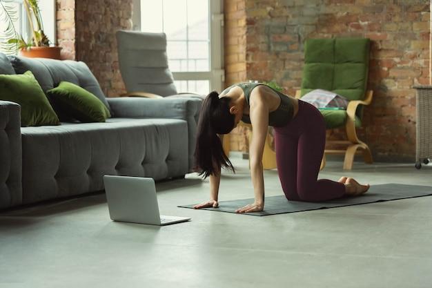 ストレッチ。自宅でプロのようにヨガのアーサナを練習するスポーティな美しい若い女性。