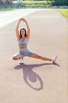 体を片側に傾けて脚の筋肉を伸ばします。灰色のスポーツウェアを着た女性は、片方の足を反対方向に伸ばしながら、片側に一歩踏み出します。正面からのショット