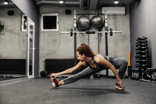 다리 근육 스트레칭. 운동복에 맞는 여성과 좋은 몸매는 체육관에서 몸 전체의 근육과 몸의 핵심을 늘립니다. 엉덩이와 다리 확장
