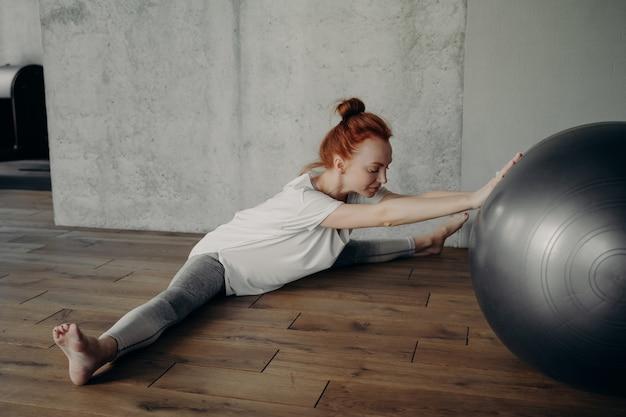 스트레칭 훈련. 맨발로 바닥에 쪼개진 자세로 앉아 꼬기를 연습하고 근육의 느낌에 집중하는 동안 피트니스 스튜디오에서 핏볼로 운동하는 젊고 스포티한 여성