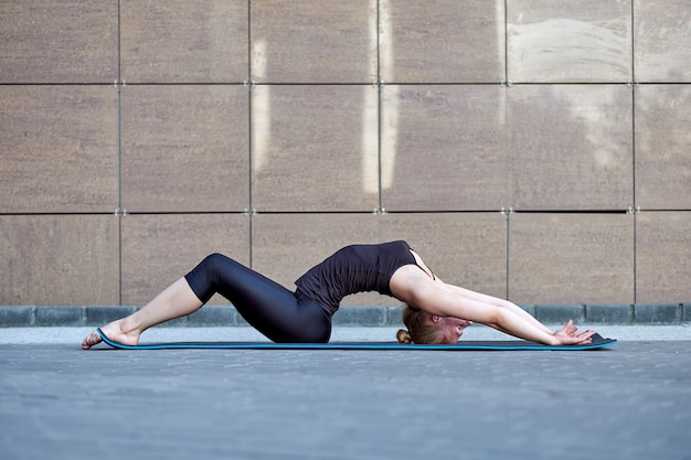 Stretching woman. fitness or gymnast or dancer doing exercises on brown wall city urban background