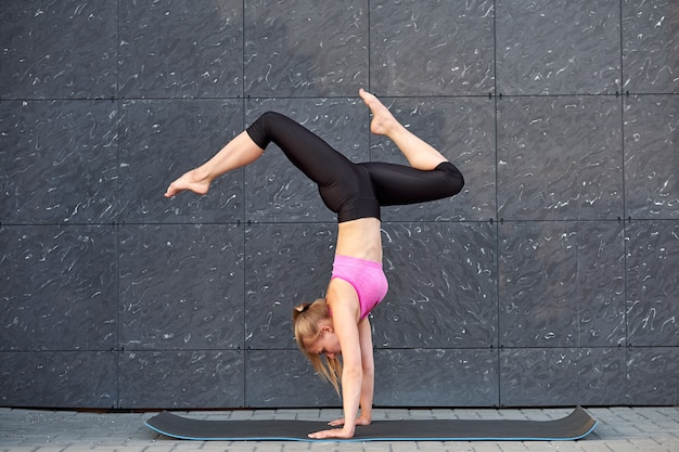 Stretching woman. fitness or gymnast or dancer doing exercises handstand on gray wall uban background. girl is standing on his hands