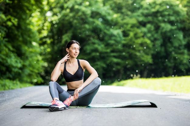 Протягивая женщина в упражнениях на открытом воздухе, улыбаясь, делая упражнения йоги, простирается после бега.