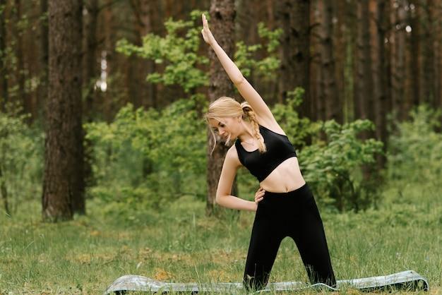 ヨガをやって幸せに笑って屋外運動でストレッチ女性