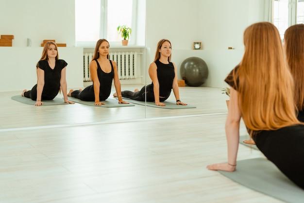 ストレッチ運動。黒い制服を着た若い女の子のグループは、ジムでストレッチトレーニングを行っています。アクロヨガ、ヨガ、フィットネス、トレーニング。