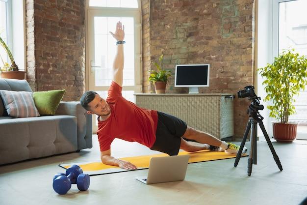 ストレッチ。コロナウイルスの発生の検疫中に自宅でトレーニングし、フィットネス、有酸素運動を行う若い白人男性。ビデオの録画またはオンラインストリーミング。ウェルネス、スポーツ、運動の概念。