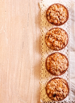 Streusel muffins over napkin on wooden surface