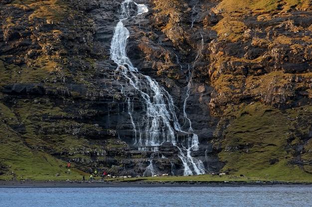 Стреймой, фарерские острова. водопад и отара овец у села саксун