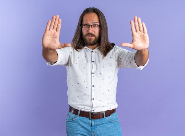 Строгий взрослый красавец в очках, смотрящий в камеру, делает стоп-жест, изолированный на фиолетовой стене
