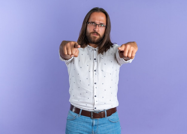 Strict adult handsome man wearing glasses looking and pointing at camera