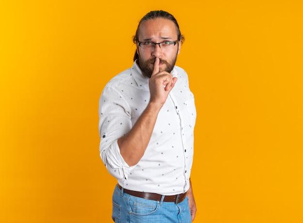 沈黙のジェスチャーをしている縦断ビューで立っている眼鏡をかけている厳格な大人のハンサムな男