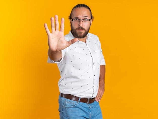 Строгий взрослый красавец в очках, стоящий в профиле, держа руку на талии, делая стоп-жест
