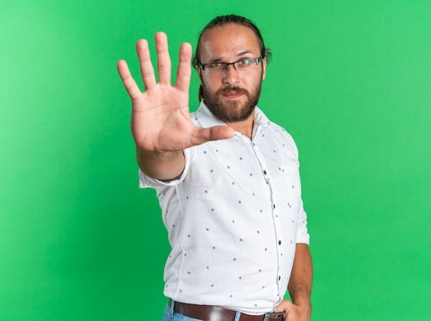 Строгий взрослый красавец в очках, стоящий в профиль, держа большой палец на поясе, делая стоп-жест