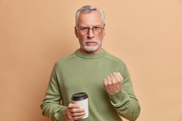 厳格な怒っているひげを生やした年配の男性が真剣に正面を見て、茶色の壁に対してカジュアルなジャンパーポーズを着ている使い捨てのコーヒーを持っていることを警告しようとします