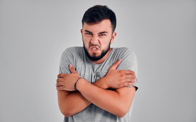 Строгий сердитый молодой человек в серой футболке, взявшись за скрещенные руки, изолирован на сером стенном фоне в студии. здоровый образ жизни моды, искренние эмоции людей, концепция холодного сезона.