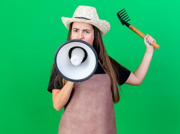 Строгая красивая девушка-садовник в униформе в садовой шляпе говорит в громкоговоритель и поднимает грабли, изолированные на зеленом