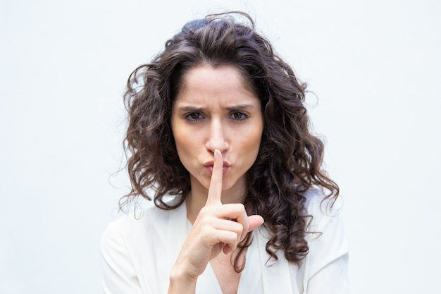 Strict beautiful woman making shh gesture