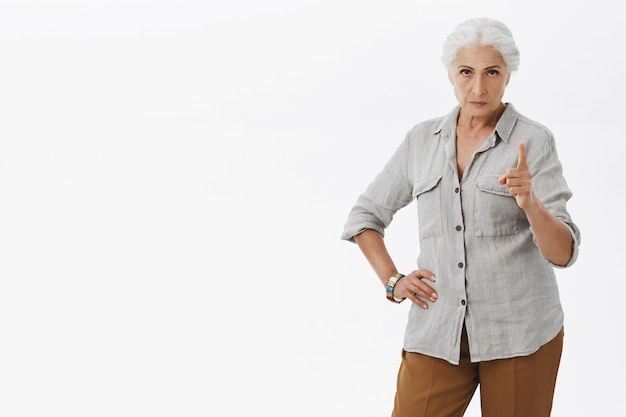 Strict and bossy granny scolding person, shaking finger angry with disapproval