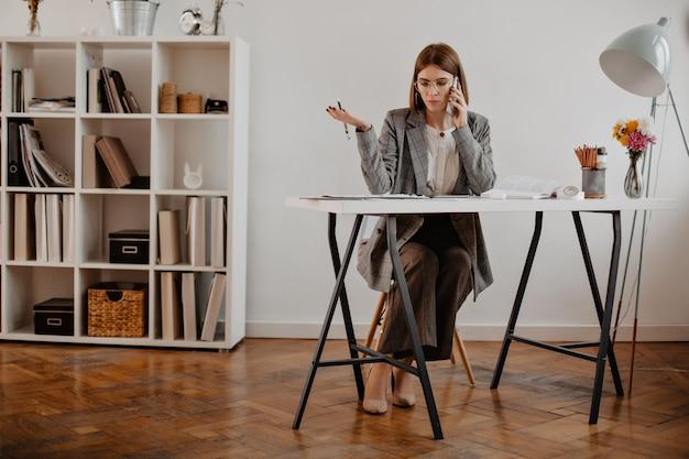 엄격한 비즈니스 여자는 그녀의 밝은 사무실에 앉아 전화로 고객과 협상합니다.