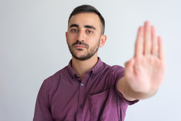 Strict businessman in casual gesturing stop