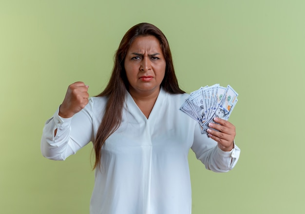 현금을 들고 올리브 녹색 벽에 고립 된 주먹을 올리는 엄격한 캐주얼 백인 중년 여성